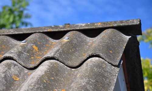 Blue sky over the dangerous asbestos old roof tiles